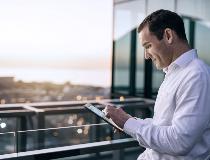 Businessman using a tablet on a balcony