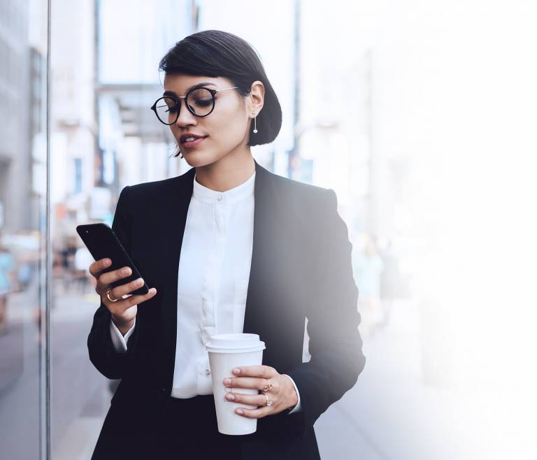 Businesswoman walking looking at her phone holding a coffee