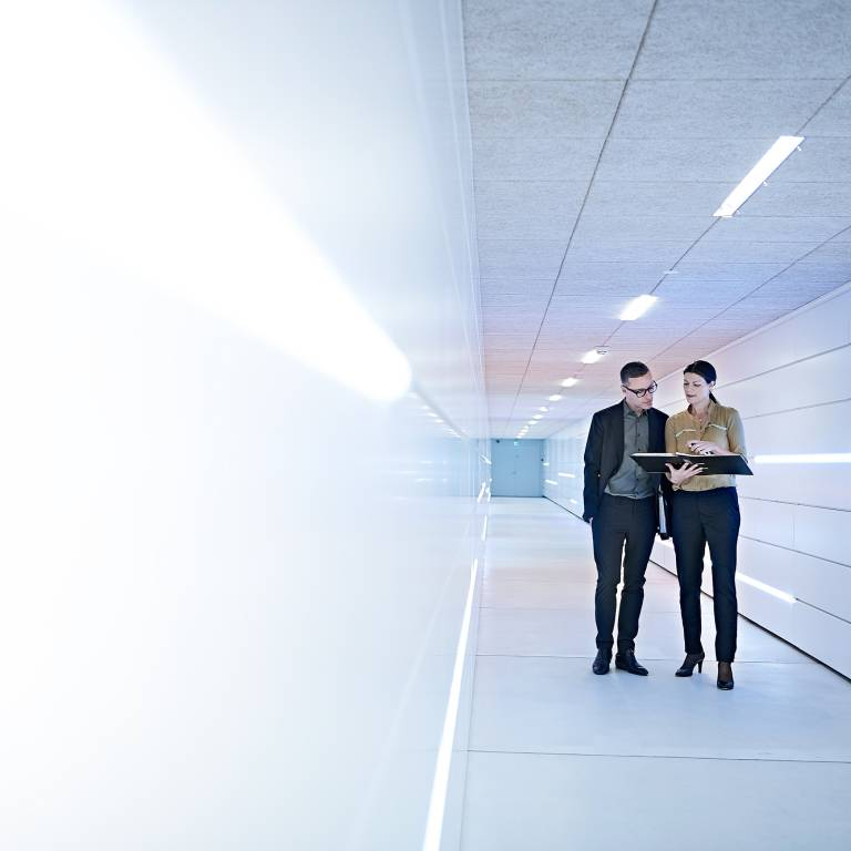 Two businesspeople looking at a notebook while walking down a white hallway